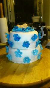 kage med blå blomster og sovende baby i stor blomst på toppen.